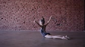 kolano : Beautiful fit gymnast girl doing gymnastic exercises in brick design studio - doing splits, coups on the floor. Slow motion