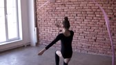 ginasta : Little girl in blacksuit practicing rhythmic gymnastic moves with a pink ribbon in training studio. Back side footage Vídeos