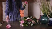 piwonie : Adult florist master arranging the big assortment flowers and plants on the counter for the future composition. Workshop, designing flowers, handcraft concept. Fireplace on the background Wideo