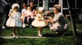 finding : Pretty little girls in yellow dresses give all of their chocolate Easter eggs to their mother in 1961.