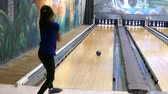 bodování : A shot of a young Asian girl throwing a bowling ball and hitting the pins down in a bowling alley.