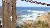 colar : A cross hanging on a fence by the ocean blows in the breeze at Big Sur, California.