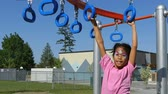 ctižádost : A cute little 9 year old Asian girl with her face painted enjoys the challenge of climbing on the playground structure. Dostupné videozáznamy