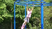 ctižádost : A cute little 9 year old Asian girl enjoys the challenge of climbing on the monkey bars at the playground.