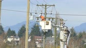 postroj : A hydro repair lineman in an orange jumpsuit and hard hat repairs a problem on the line in the city of Vancouver.