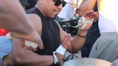 vurmalı : A djembe drummer with a large Mohawk lays down a funky beat at the Drum Circle at Venice Beach, California. Stok Video