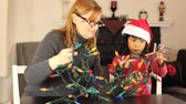 emaranhado : A mother and daughter have fun together trying to untangle the Christmas lights in preparation for trimming the tree.