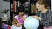 ano : A homeschool mom teaches a geography lesson to her cute 7 year old Asian daughter using a globe.