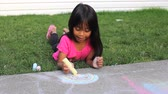 křída : A cute little Asian girl enjoys creating some pretty sidewalk chalk art on a lovely summer day.