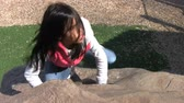 udatnost : A cute determined Asian girl climbs up the face of a rock at the local playground in the spring.