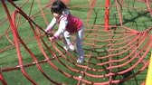 udatnost : A cute Asia girl successfully climbs a large spider web at the playground.