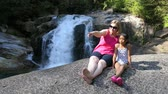 britânico : A cute little 9 year old Asian girl enjoys spending time with her Mom while hiking in the woods and discovering a beautiful waterfall on a gorgeous sunny summer day.