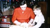 A woman in a bright red dress gets a brand new pink jacket for Christmas in Cleveland, Ohio in 1956. Stok Video