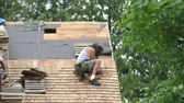 madeira compensada : A scruffy roofer hammers down a cedar shake shingle on an old home that is being restored. Stock Footage
