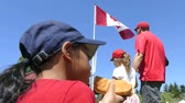 A cute little Asian girl enjoys a yummy hot dog as she celebrates Canada Day in Vancouver. Stok Video