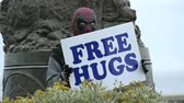 A man wearing a Deadpool mask holds a sign offering free hugs to the public. Stok Video