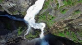 hardanger : Aerial top-down view of popular Voringfossen waterfall in Norway with visible rainbow on sunny summer day, major tourist attraction on the way down from Hardangervidda. Aerial 4k Ultra HD. Stock Footage