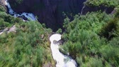 hardanger : Flight above small river which turns into massive tall waterfall Voringfossen waterfall in Norway, popular major tourist attraction. Aerial 4k Ultra HD.