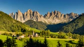 val di funes : Sunny day turns into night in this timelapse footage of St Magdalena church in Italian Alps with white peaks of Dolomites towering above the picturesque landscape.