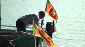 bo : Asia Sri Lanka Maligawa November 19, 2013 goda.Aziat fumbling in boat on background of two flags of Sri Lanka