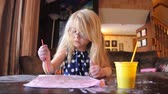 suluboya : A preschool girl is painting on messy white paper at desk in her house for an artistic or creative concept.