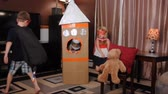 imaginar : A mother and her children are playing with a cardboard box of a rocket ship in their home and pretending they are in space for an activity or entertainment concept.