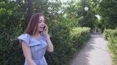 bom humor : Beautiful woman walking in the park and talking on the phone. Stock Footage