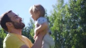 поднимать : Young father playing and throwing up his little daughter outdoors. Стоковые видеозаписи