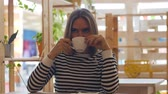 Young thoughtful woman smiling and drinking coffee in cafe. Stok Video