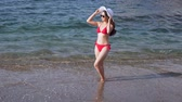kazak : Woman dressed in red swimwear stands in water on beach.