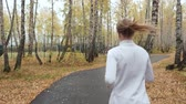 dürtmek : Young blonde woman running in the autumn park. Stok Video