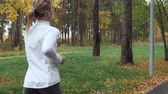 kocogás : Young sporty woman running in the autumn park. Stock mozgókép