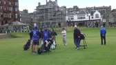 hráč golfu : Golfers and caddies meet at the Old Course at St Andrews - These golfers from all over the world took part in a golf course on the Old Course at St Andrews. The Old Course is one of the few golf courses in the world that still has a real caddy program.