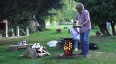 repousante : Over the campfire fried eggs are prepared by the man who serves his wife