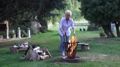 repousante : Over the fire in a fire basket are prepared by the blond woman grill sausages Vídeos