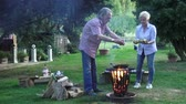 repousante : A funny couple preparing the eggs over the campfires in the fire basket Vídeos