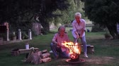 repousante : Attractive couple enjoying the romantic evening around the campfire and grilling sausages Vídeos