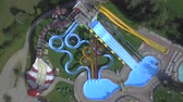 AERIAL: Flying above big extreme waterpark with water slides and pools Stok Video