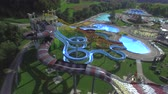 AERIAL: Flying around big extreme water park with waterslides toboggans and pools