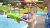 SLOW MOTION CLOSE UP: Father and son playing same team of water gun fight, squirting water with water guns