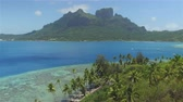 AERIAL: Flying above beautiful Bora Bora island resort with famous mountain on the main island and dreamy blue lagoon in sunny summer