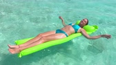 vor : SLOW MOTION CLOSE UP: Smiling woman in bikini laying and tanning on air bed raft floatie on turquoise ocean water surface in Pacific island paradise