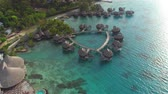 polinésia : AERIAL: Flying above big luxury waterfront hotel on beautiful white sandy beach with deluxe overwater bungalows, fancy restaurants and outdoors swimming pool overlooking the perfect turquoise blue lagoon