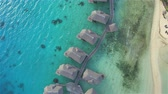 AERIAL: Luxury overwater bungalows and beachfront villas facing sparkling turquoise-blue waters of premium exotic beach on beautiful tropical island in the middle of blue lagoon in exquisite Bora Bora, offering a perfect honeymoon vacation Stok Video