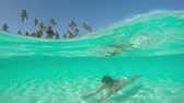 sandy bottom : SLOW MOTION HALF UNDERWATER CLOSE UP: Young woman in colorful bikini swimming under water surface in amazing crystal clear blue lagoon in front of beautiful tropical island on perfect summer day Stock Footage