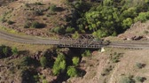 enrolamento : AERIAL: Countryside road and old river bridge in sunny rocky desert