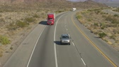 AERIAL SLOW MOTION CLOSE UP: Cars and trucks driving on busy highway through the desert. Freight semi trucks transporting goods, personal cars on a road trip, people traveling in sunny summer