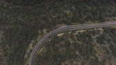 zigzag : AERIAL: Black SUV  driving along the winding mountain pass road through the forest. People travelling, road trip on curvy road through beautiful countryside scenery in sunny summer