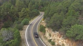 zigzag : AERIAL: Black SUV jeep car driving along the winding mountain pass road through the forest. People traveling, road trip on curvy road through beautiful countryside scenery in sunny summer