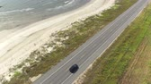 louisiana : AERIAL: Black SUV car driving on countryside road along the Bay of Mexico. People traveling, road trip on empty road through beautiful countryside scenery in sunny summer